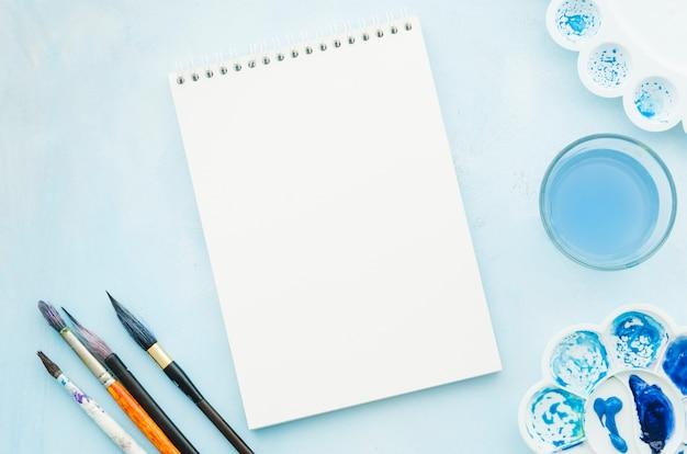Caderno de vista superior com pincéis e aquarela