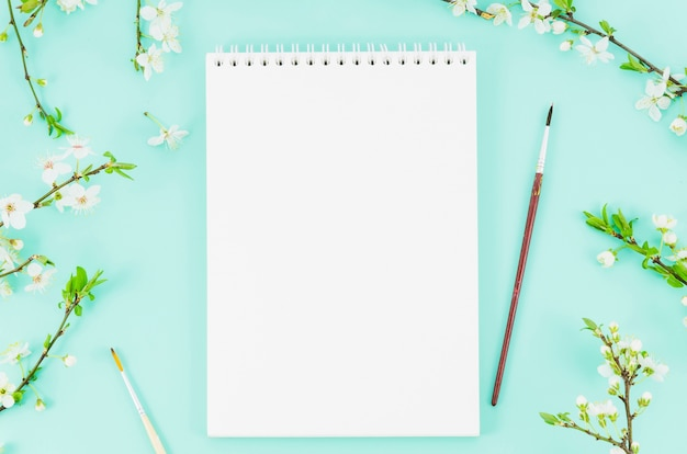 Caderno de vista superior com ramos de flores