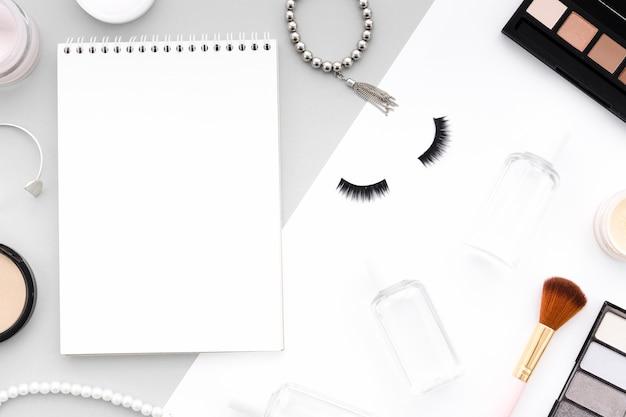 Caderno de vista superior rodeado de maquiagem