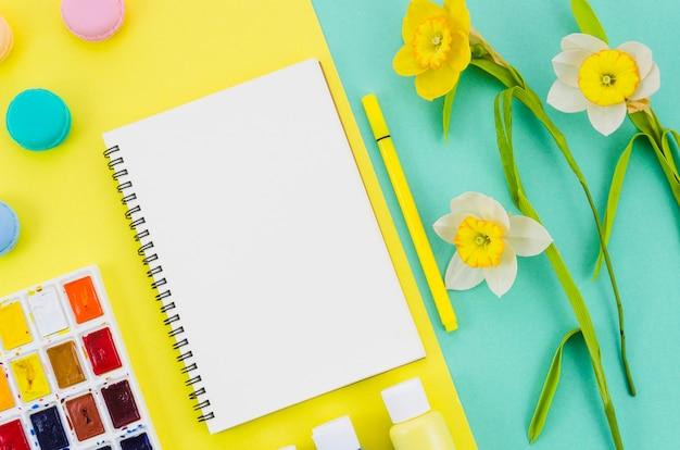 Caderno de vista superior rodeado por elementos de pintura