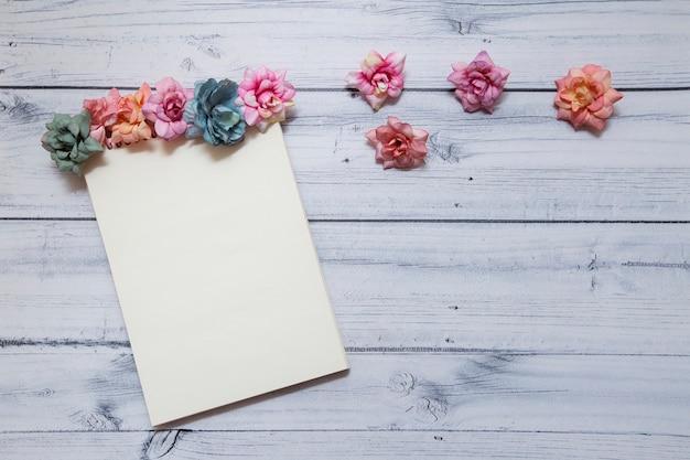 Caderno decorado com flores multicoloridas em um fundo de madeira. vista de cima. conceito para 8 de março e a primavera.