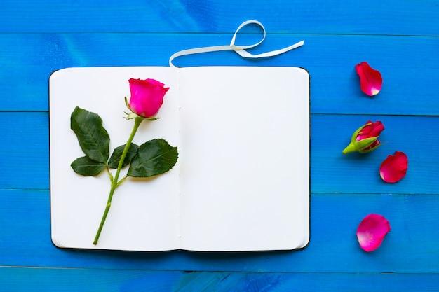 Caderno diário com rosa sobre fundo azul de madeira.