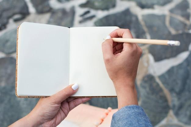 Caderno do papel em branco e mãos da mulher com lápis de madeira para escrever.