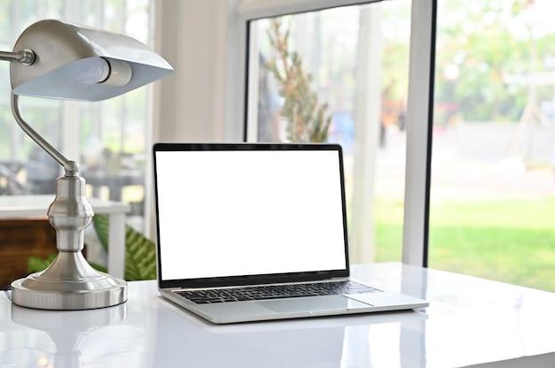 Caderno do portátil e lâmpada na tabela.