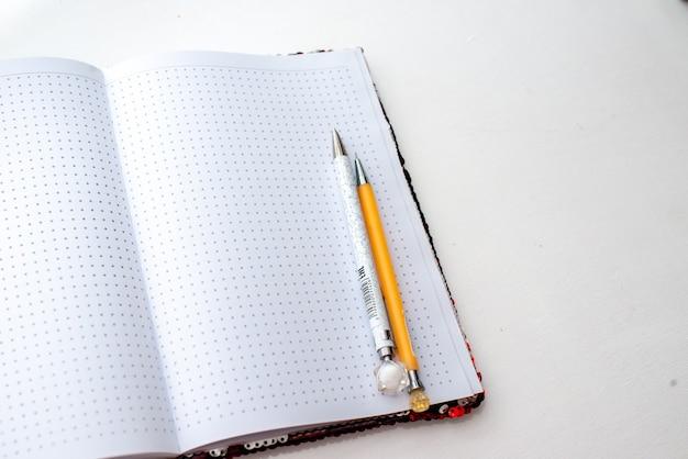 Caderno dourado com lantejoulas com uma caneta