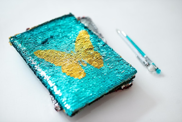 Caderno dourado com lantejoulas com uma caneta Foto Premium