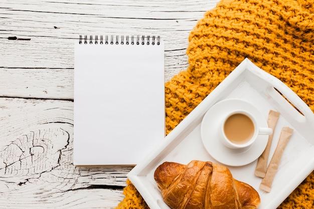 Caderno e bandeja com café da manhã
