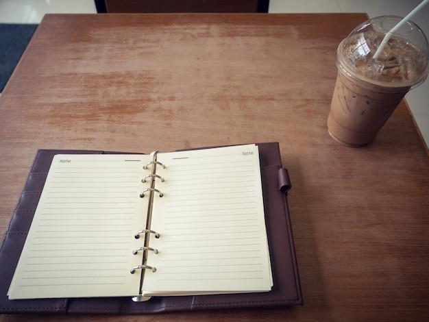Caderno e café gelado no fundo de madeira