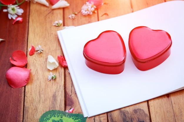 Caderno e caixa de coração vermelho com pétalas de flores decorativas na mesa de madeira.