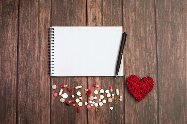 Caderno e caneta com coração vermelho e pílulas na madeira