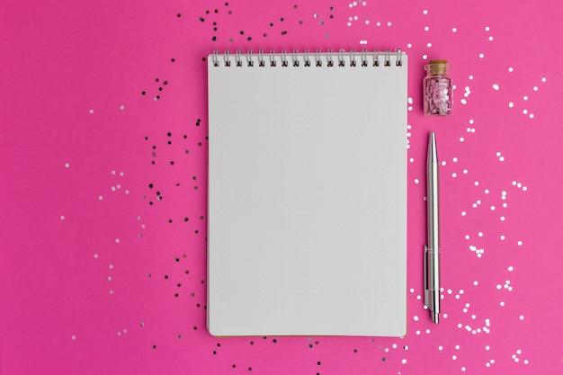 Caderno e caneta na superfície rosa