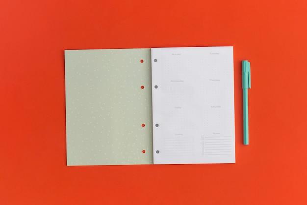 Caderno e caneta sobre fundo vermelho. vista do topo. postura plana. de volta ao conceito de escola.