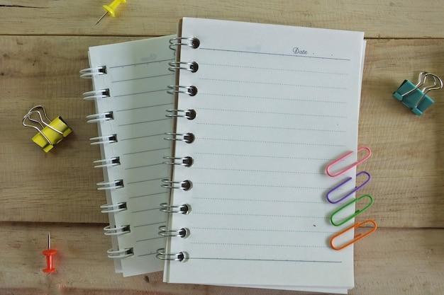 Caderno e clipes de papel no fundo de madeira