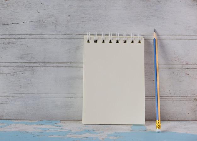 Caderno e lápis amarelo no fundo da mesa de madeira azul vintage