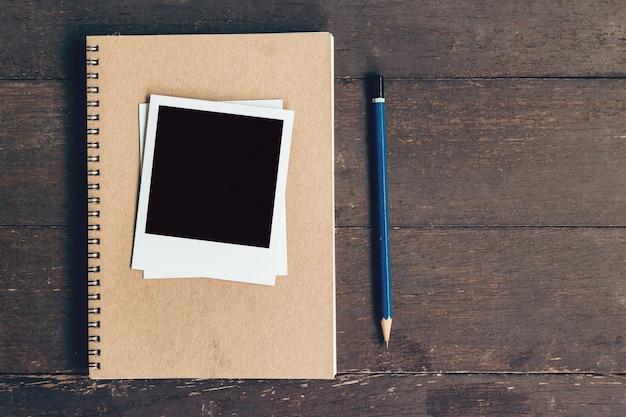 Caderno e lápis com quadro foto no fundo da mesa de madeira com espaço