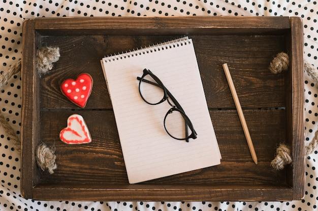 Caderno e lápis na bandeja de madeira