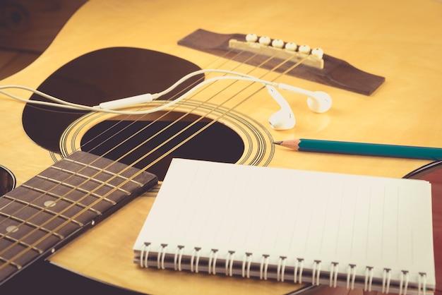 Caderno e lápis na guitarra, escrevendo música, vintage