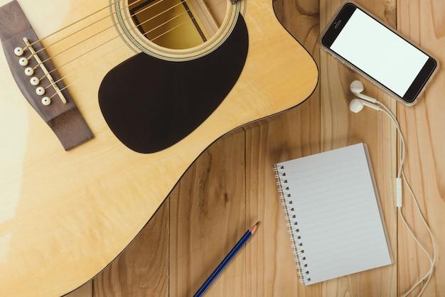 Caderno e lápis na guitarra, escrevendo música