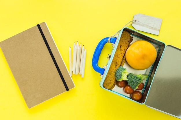 Caderno e lápis perto de lancheira aberta