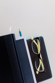Caderno e livros com uma caneta e óculos estão sobre a mesa. educação. o negócio. trabalhos.