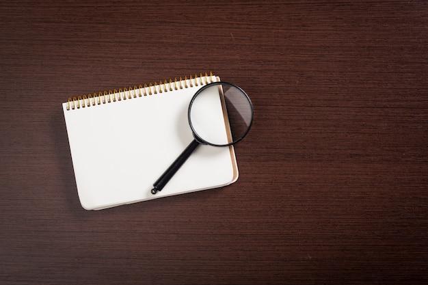 Caderno e lupa em um de madeira