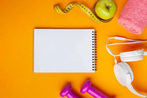 Caderno e maçã lisos do plano no fundo amarelo
