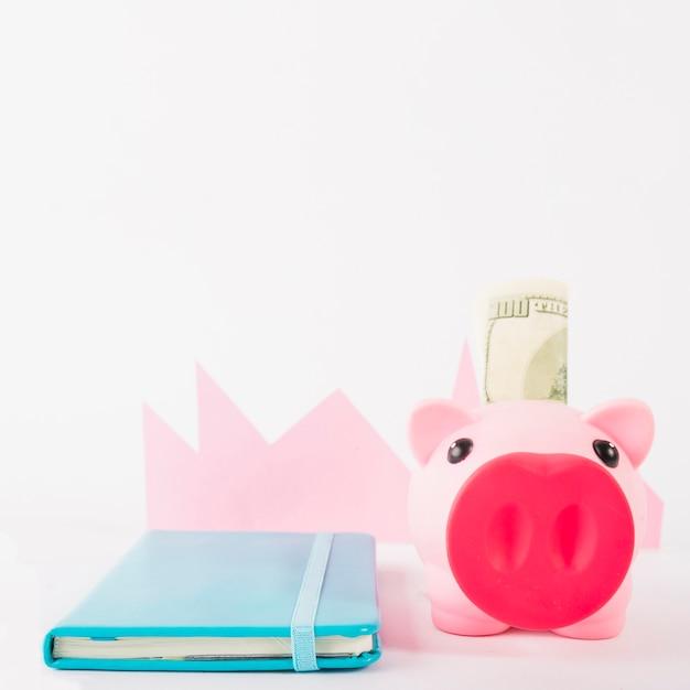 Caderno e mealheiro com dinheiro no fundo branco