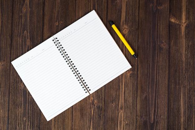 Caderno e papel branco vazio com caneta na madeira