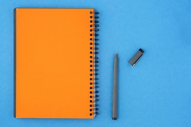Caderno e pena vazios amarelos com um tampão aberto em um fundo azul.