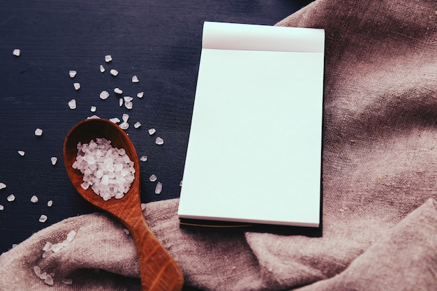 Caderno e sal marinho em colher de pau