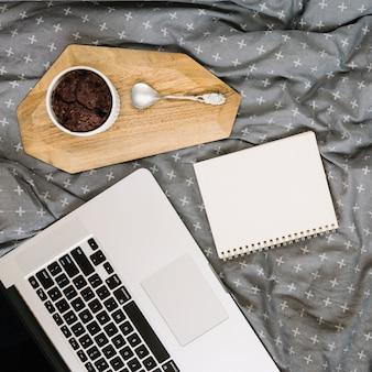 Caderno e sobremesa perto de laptop
