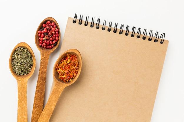 Caderno e variedade de especiarias em colheres de madeira