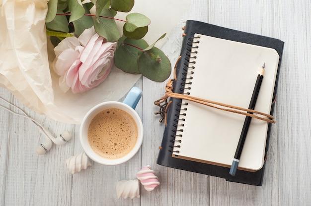 Caderno em branco aberto, buquê, xícara de café, fones de ouvido