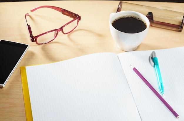 Caderno em branco aberto com café