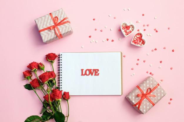 Caderno em branco aberto com caixa de presente, flores e corações em um fundo rosa
