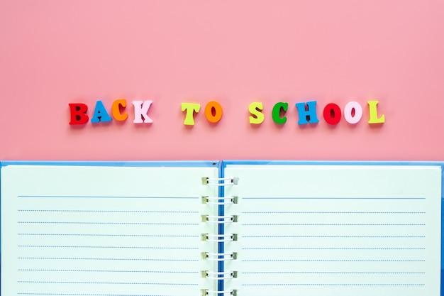 Caderno em branco aberto com texto de madeira volta à escola em fundo rosa