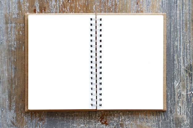 Caderno em branco aberto em uma vista de mesa de madeira