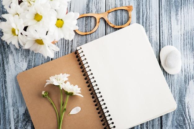 Caderno em branco aberto, seixos, flores