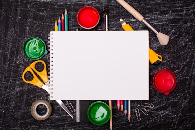 Caderno em branco aberto sobre material escolar na parede de um quadro-negro