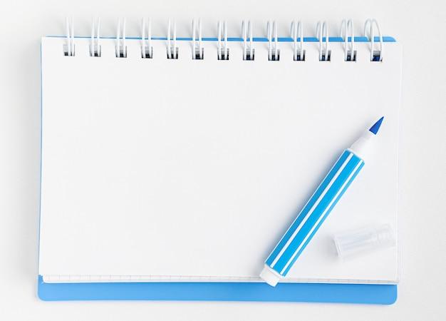 Caderno em branco branco e marcador azul no branco. vista superior, maquete.