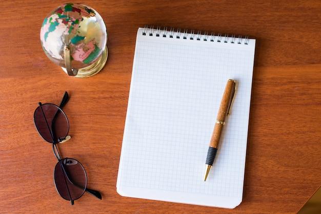 Caderno em branco branco papel e globo, óculos escuros, mapa-múndi em fundo de madeira