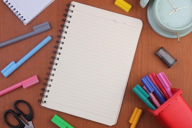 Caderno em branco cercado por papelaria isolado em um fundo de madeira