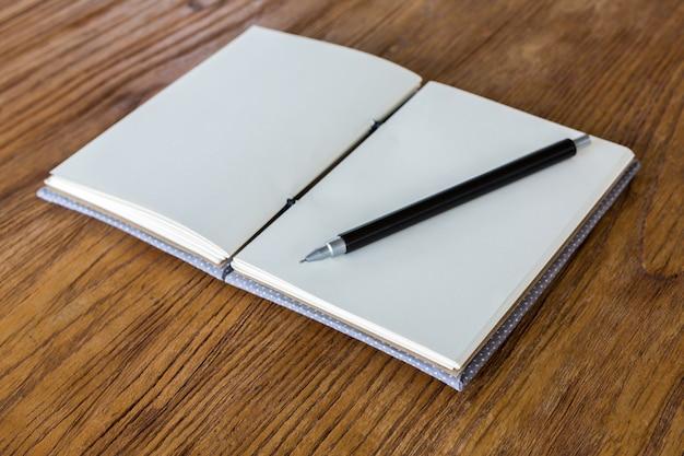 Caderno em branco com a pena na mesa de madeira