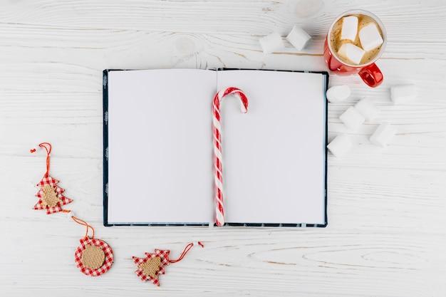 Caderno em branco com bastão de doces na mesa