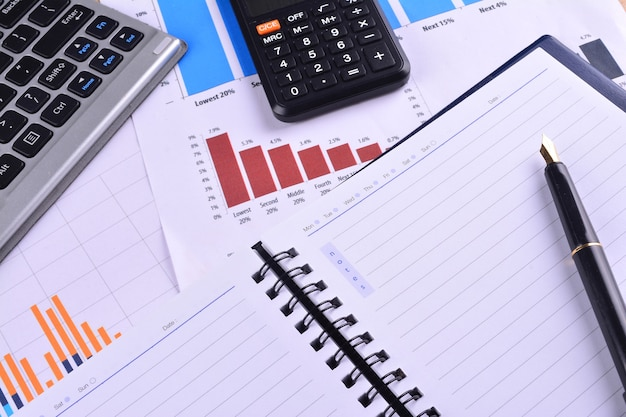 Caderno em branco com calculadora, teclado e caneta-tinteiro em gráficos, tabelas e mesa de negócios. o local de trabalho dos empresários