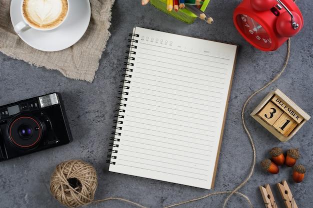 Caderno em branco com câmera vintage, café, relógio vermelho e lápis