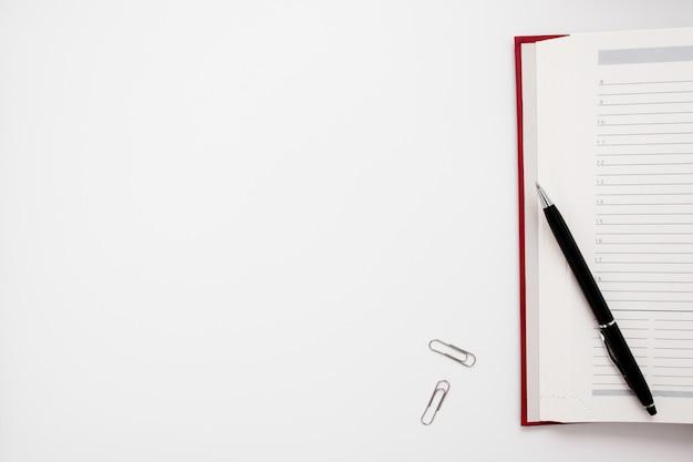 Caderno em branco com caneta e clipes