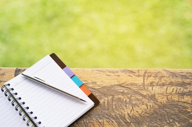 Caderno em branco com caneta e lápis na mesa de madeira, conceito de negócio