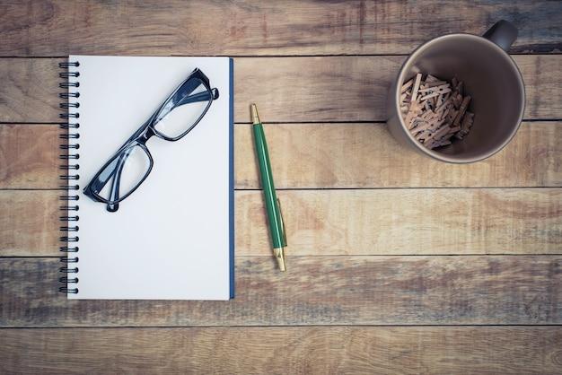 Caderno em branco com caneta e óculos em fundo de madeira
