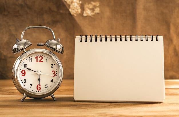 Caderno em branco com despertador na mesa de madeira.